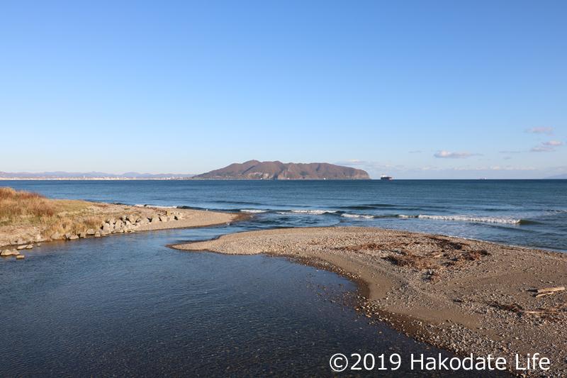 茂辺地川河口付近と函館山